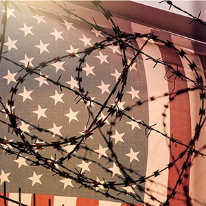 American Flag behind barbbed wire