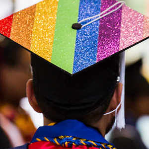 LGBTQ Graduate with rainbow inspired cap.